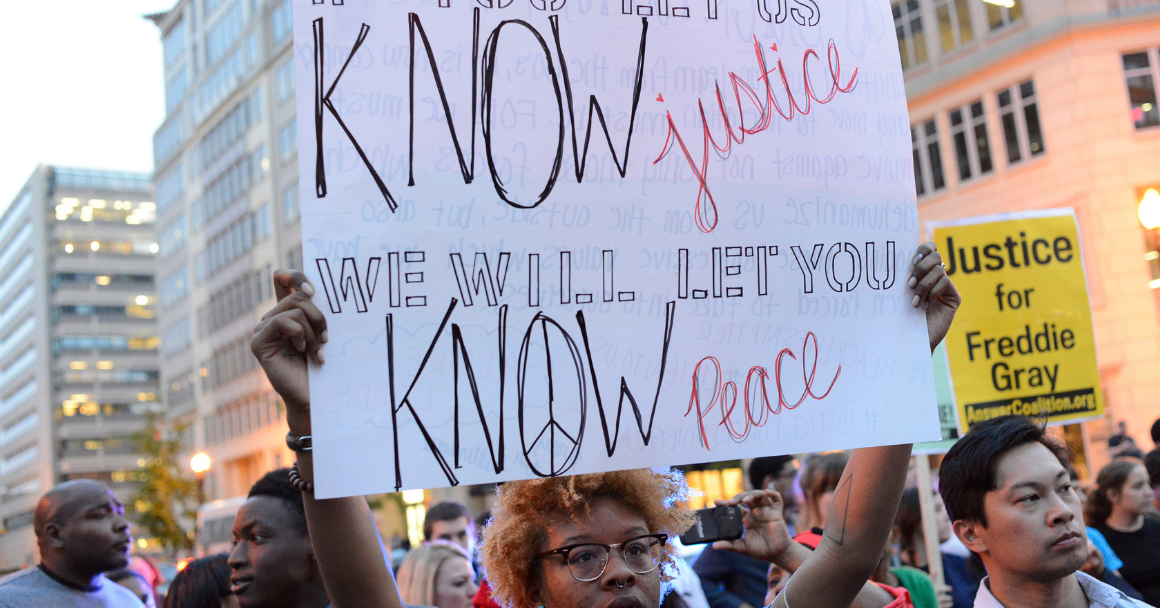 """a Black protester holding a sign that says """"if you let us know justice, we will let you know peace"""""""