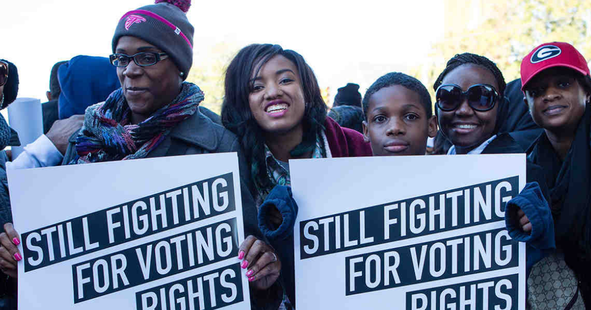 "a group of black voters held signs that say ""still fighting for voting rights"""