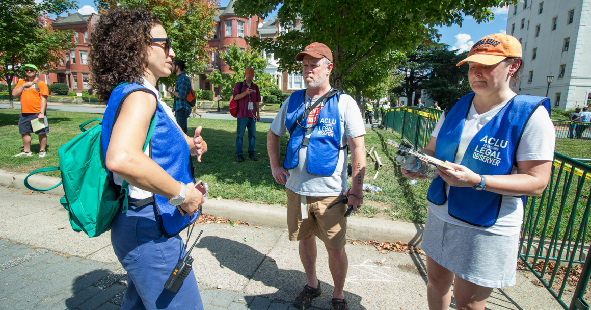 Volunteer legal observers stand in a circle, sharing notes.